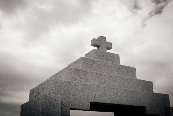 A black and white photo of a concrete sculpture with a cross on top.